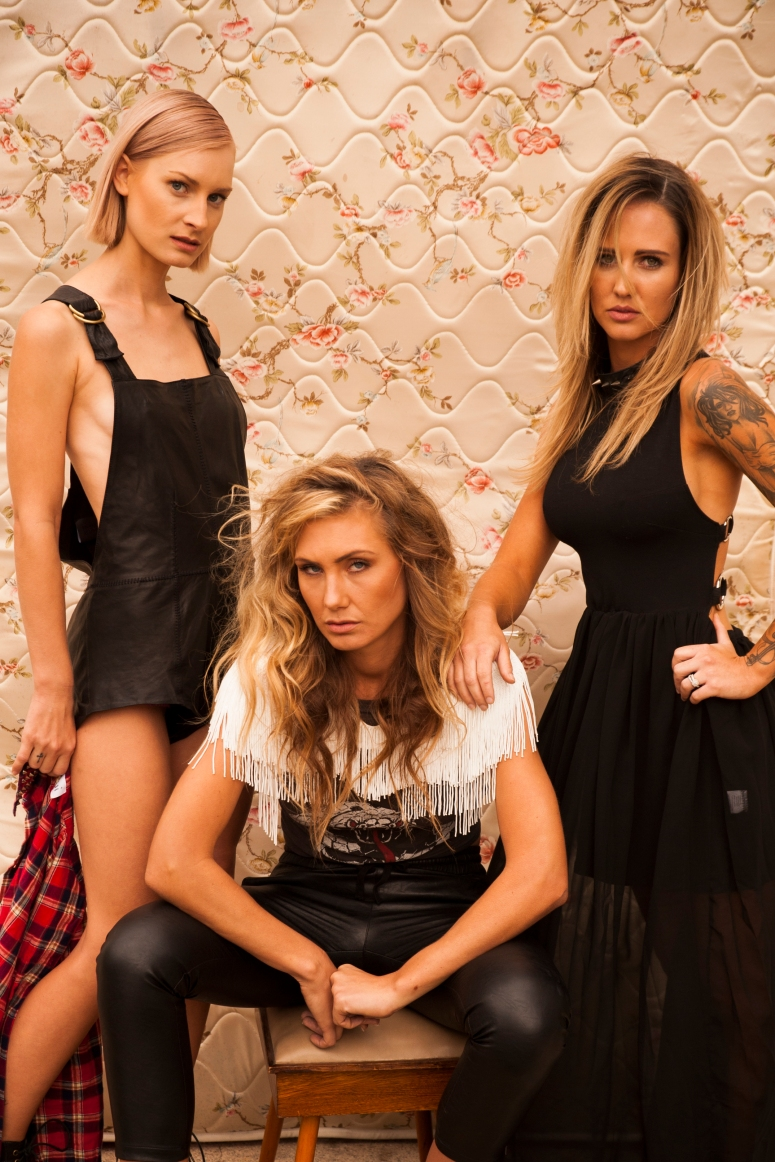 ASH (left) FOM leather overalls, Princess Polly studded flanno, SARAH (centre) Sass & Bide white beaded shoulder piece, vintage band teee, Camilla & Marc pants, stylists own stilettos, BRITT (right) Bitching And Junkfood maxi dress, Doc Martins.